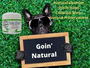 """Image of dog on grass holding sign """"Goin' Natural with a container of PawPurity Tear Stain Remover Wipes next to him."""