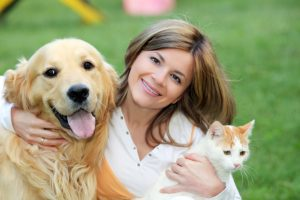 Woman with dog and cat indicating PawPurity offers natural uni-pet care products